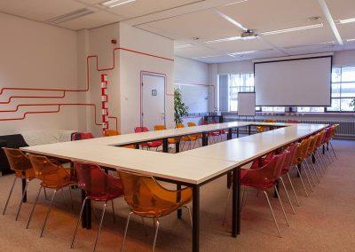 vergaderruimte oranje rood doorzichtige stoelen lijnenspel op muur rood