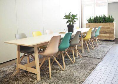 third-place-at-school-huiskamer-welkomstgevoel-op-school-door-eettafels-met-fris-gekleurder-kuipstoeltjes-en-groot-kleed-door-INinterieurs