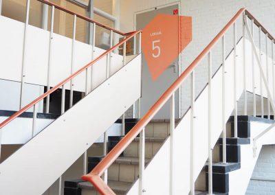 trappenhuis-kleurvlak-op-deur-voor-veelzijdig-onderwijs-beeldmetafoor-interieurconcept-storytelling-INinterieurs